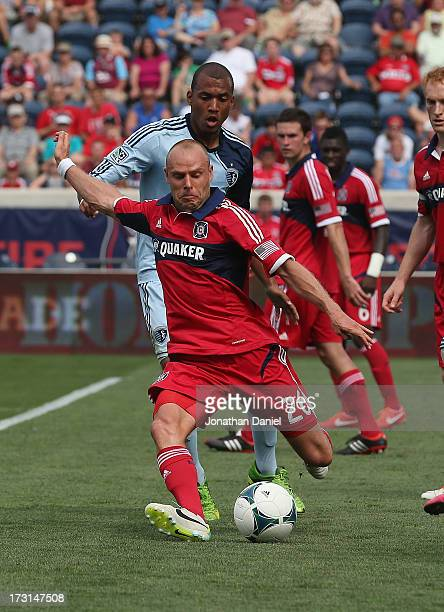 Joel Lindpere of the Chicago Fire passes the ball in front of Teal Bunbury of Sporting Kansas City during an MLS match at Toyota Park on July 7 2013...