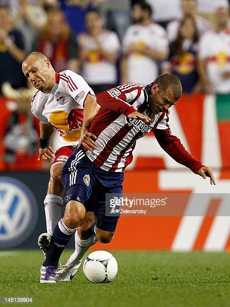 Joel Lindpere of the New York Red Bulls fights for the ball with Alejandro Moreno of the Chivas USA during their match at Red Bull Arena on May 23...