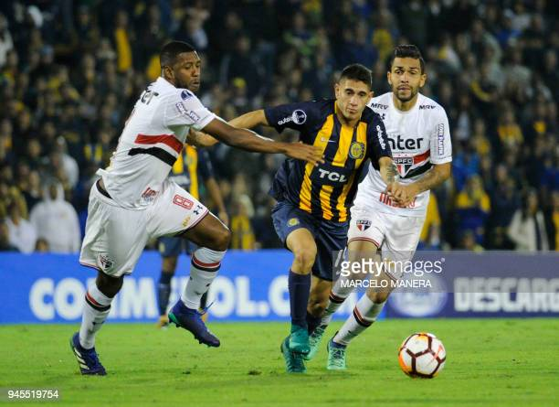 Joel Lopez of Argentinian Rosario Central vies for the ball with Jucilei of Brazilian Sao Paulo during a Copa Sudamericana 2018 football match at the...