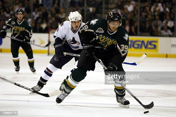 Joel Lundqvist of the Dallas Stars works the puck in front of Taylor Pyatt of the Vancouver Canucks during the 1st period of game three of the 2007...