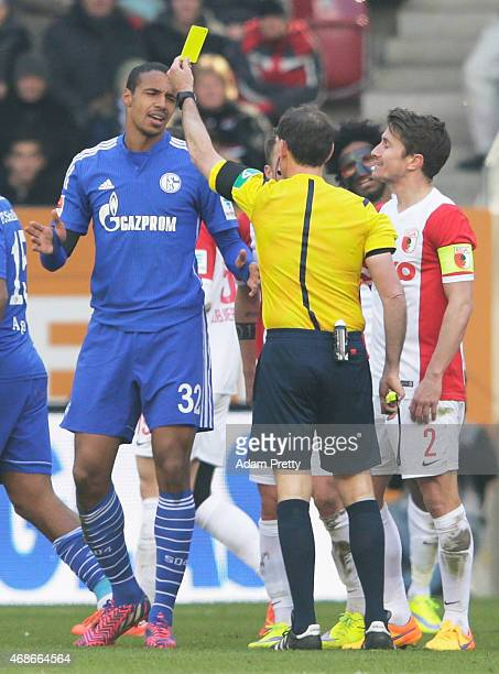Joel Matip of FC Schalke is shown a yellow card during Bundesliga match between FC Augsburg and FC Schalke 04 at SGL Arena on April 5 2015 in...