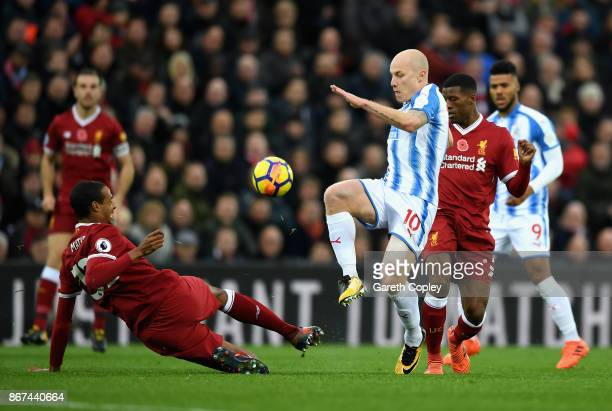 Joel Matip of Liverpool and Aaron Mooy of Huddersfield Town battle for possession during the Premier League match between Liverpool and Huddersfield...