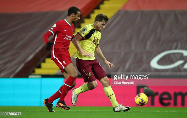 Joel Matip of Liverpool battles for possession with Chris Wood of Burnley during the Premier League match between Liverpool and Burnley at Anfield on...