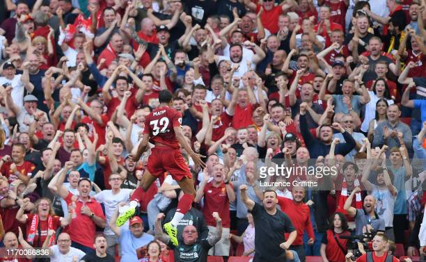 Joel Matip of Liverpool celebrates in front of the Kop after scoring the opening goal during the Premier League match between Liverpool FC and...