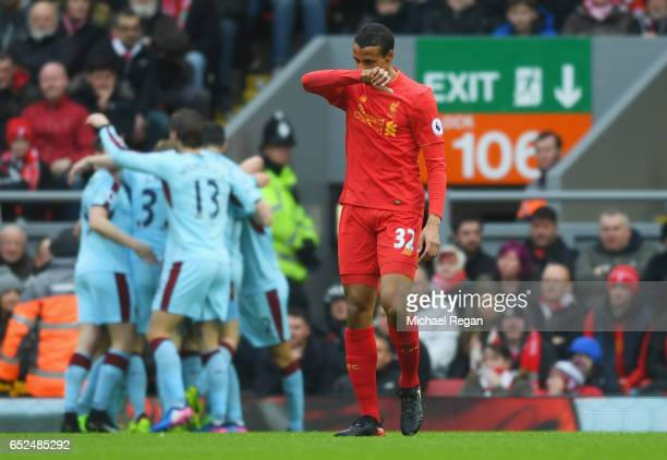 Joel Matip of Liverpool looks dejected as Bunrley players celebrate as Ashley Barnes scores their first goal during the Premier League match between...