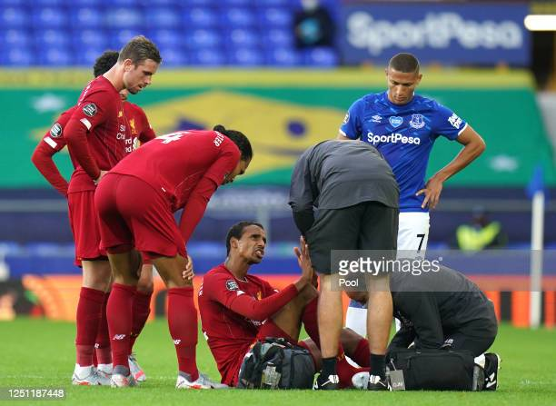 Joel Matip of Liverpool sits on the floor injured while he is seen to my his team mates and medical staff during the Premier League match between...