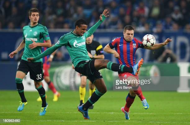 Joel Matip of Schalke challenges Adrian Popa of Steaua during the UEFA Champions League Group E match between FC Schalke 04 and FC Steaua Bucuresti...