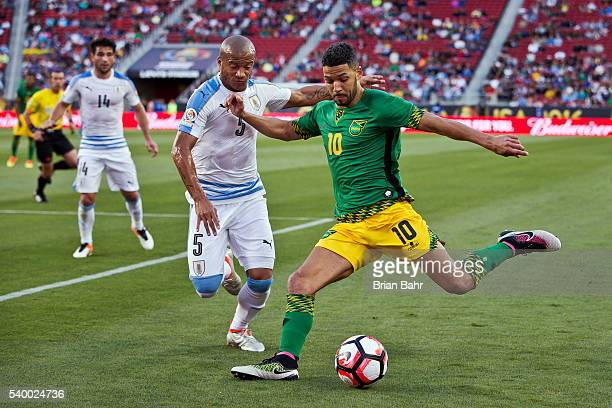 Joel McAnuff of Jamaica takes a shot as Carlos Sanchez of Uruguay defends during a group C match between Uruguay and Jamaica at Levi's Stadium as...