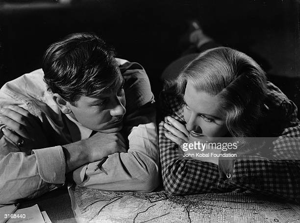 Joel McCrea as George Melville and Jean Arthur as Claire Peyton lying down with a map in a scene from 'Adventure In Manhattan' directed by Edward...