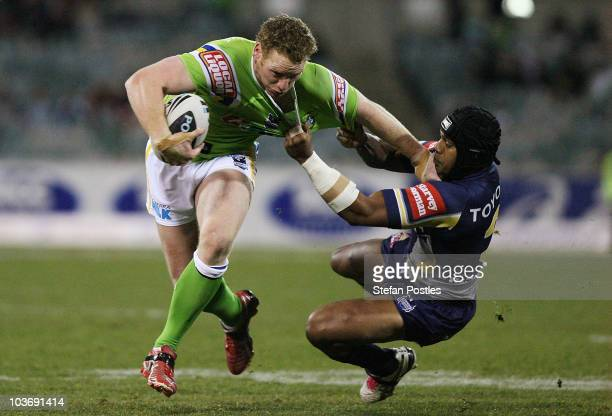 Joel Monaghan of the Raiders fends off Ty Williams of the Cowboys during the round 25 NRL match between the Canberra Raiders and the North Queensland...