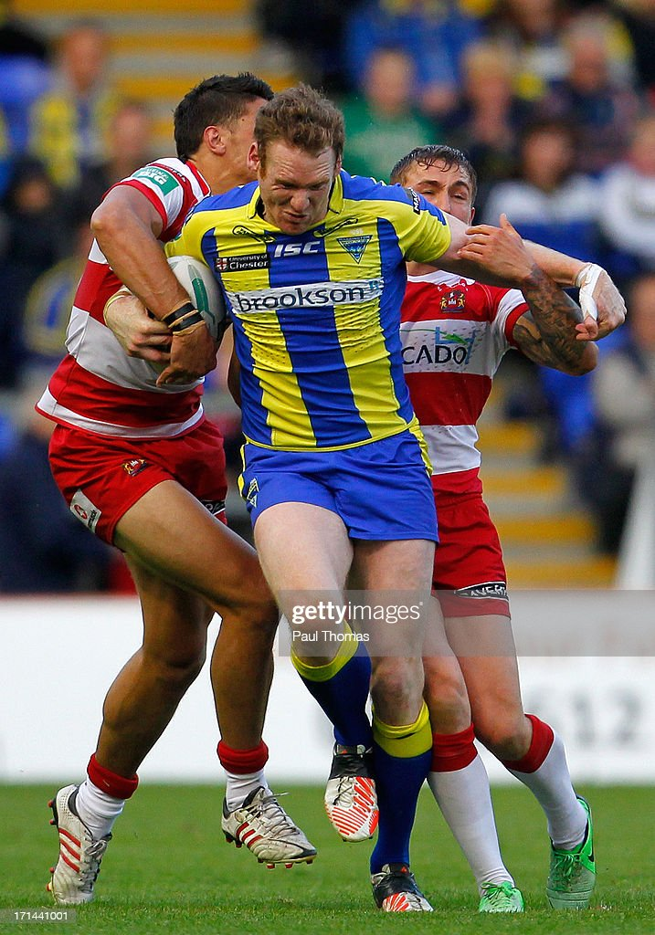 Joel Monaghan of Warrington (C) is tackled by Anthony Gelling (L) and Sam Powell of Wigan during the Super League match between Warrington Wolves and Wigan Warriors at the Halliwell Jones Stadium on June 24, 2013 in Warrington, England.