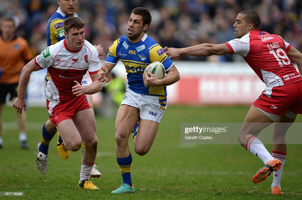 Joel Moon of Leeds gets past Liam Salter and Omari Caro of Hull KR to score his second half try during the Super League match between Hull Kingston Rovers and Leeds Rhinos at Craven Park Stadium on April 28, 2013 in Hull, England.