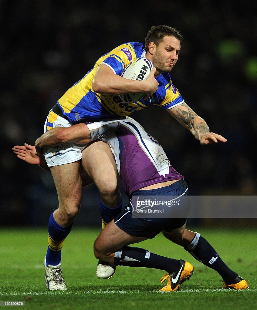 Joel Moon of Leeds Rhinos is tackled by Cameron Smith of Melbourne Storm during the World Club Challenge match between Leeds Rhinos and Melbourne Storm at Headingley Carnegie Stadium on February 22, 2013 in Leeds, England.