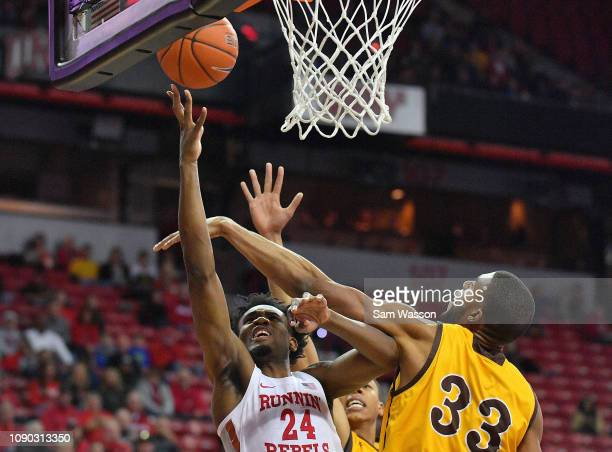 Joel Ntambwe of the UNLV Rebels scores on a layup and is fouled by Jordan Naughton of the Wyoming Cowboys during their game at the Thomas Mack Center...