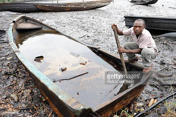 Joel Olatunde Agoi An indigene of Bodo Ogoniland region in Rivers State tries to separate with a stick the crude oil from water in a boat at the Bodo...