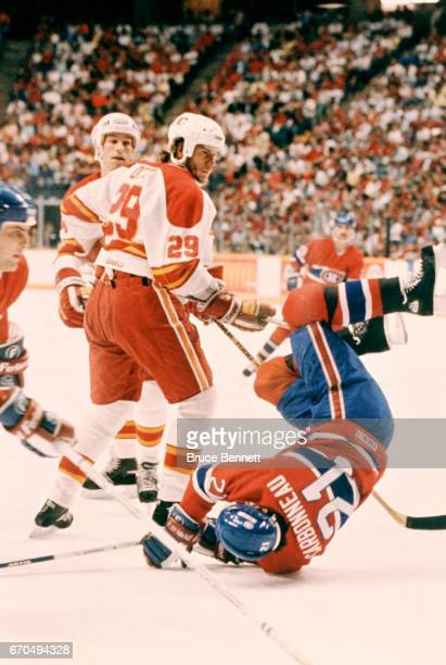 Joel Otto of the Calgary Flames trips Guy Carbonneau of the Montreal Canadiens during a game in the 1986 Stanley Cup Finals circa May 1986 at the...