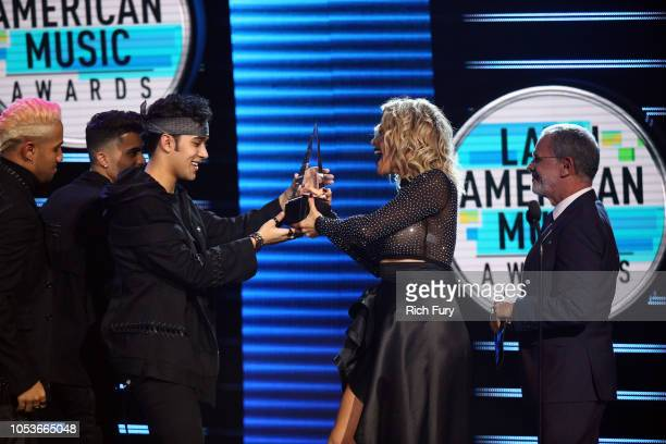 Joel Pimentel of CNCO accepts the Favorite Duo or Group award from Dayana Garroz and Tony Plana onstage during the 2018 Latin American Music Awards...