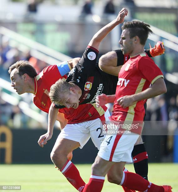Joel Pohjanpalo of Bayer 04 Leverkusen is suppended by Leandro Desabato and facundo Sanchez of Estudiantes de la Plata of Argentina while trying to...