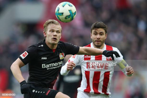 Joel Pohjanpalo of Leverkusen is challenged by Jonas Hector of Koeln during the Bundesliga match between 1 FC Koeln and Bayer 04 Leverkusen at...
