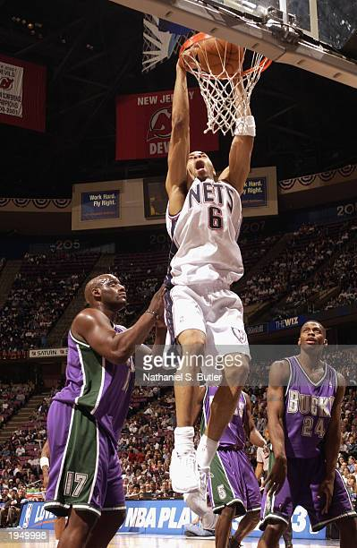 Joel Przybilla of New Jersey Nets dunks near Anthony Mason and Desmond Mason of the Milwaukee Bucks in Game one of the Eastern Conference...