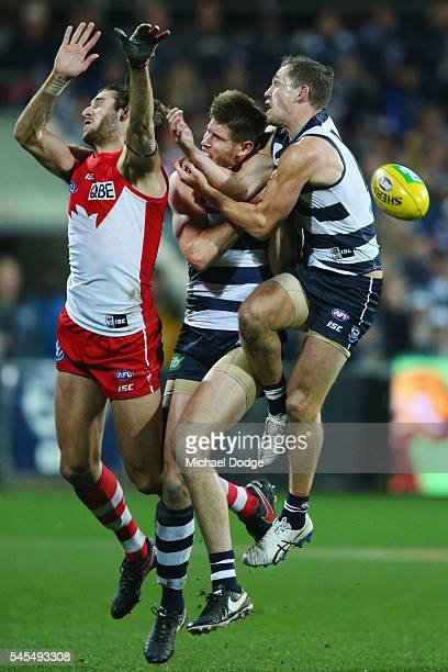 Joel Selwood of the Cats collides back into Zac Smith and Sam Naismith of the Swans during the round 16 AFL match between the Geelong Cats and the...
