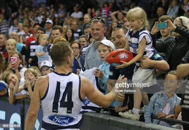 Joel Selwood of the Cats gives a football to a young girl in the crowd after winning the round three AFL match between the Geelong Cats and the...