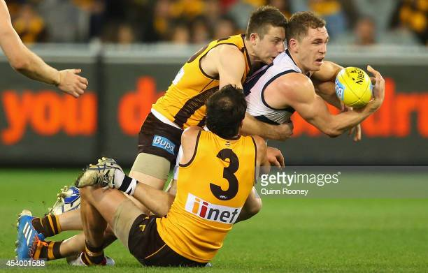 Joel Selwood of the Cats handballs whilst being tackled by Liam Shiels and Jordan Lewis of the Hawks during the round 22 AFL match between the...