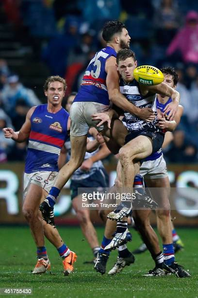 Joel Selwood of the Cats is hit by Koby Stevens of the Bulldogs during the round 16 AFL match between the Geelong Cats and the Western Bulldogs at...