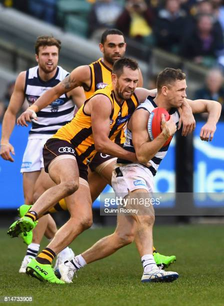 Joel Selwood of the Cats is tackled by Luke Hodge of the Hawks during the round 17 AFL match between the Geelong Cats and the Hawthorn Hawks at...