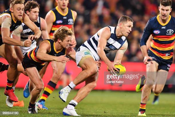 Joel Selwood of the Cats is tackled by Rory Sloane of the Crows during the round 17 AFL match between the Adelaide Crows and the Geelong Cats at...