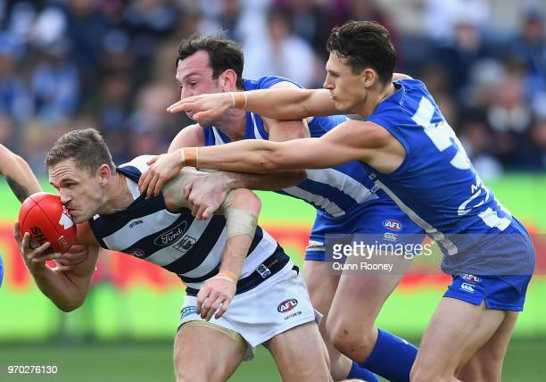 Joel Selwood of the Cats is tackled by Todd Goldstein and Ben Jacobs of the Kangaroos during the round 12 AFL match between the Geelong Cats and the...