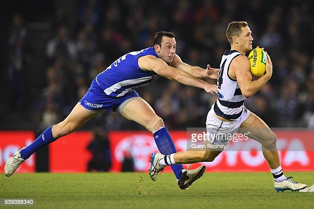 Joel Selwood of the Cats is tackled by Todd Goldstein of the Kangaroos during the round 12 AFL match between the Geelong Cats and the North Melbourne...