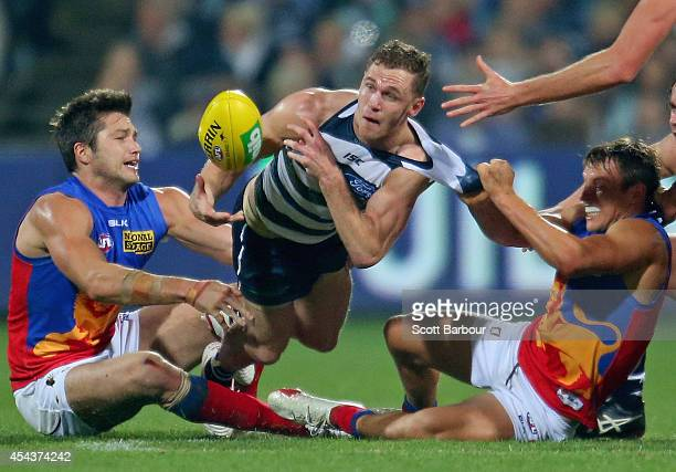 Joel Selwood of the Cats is tackled during the round 23 AFL match between the Geelong Cats and the Brisbane Lions at Simonds Stadium on August 30...