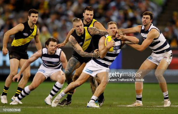 Joel Selwood of the Cats is tackled high by Dustin Martin of the Tigers ahead of Patrick Dangerfield and Ryan Abbott of the Cats and Trent Cotchin...