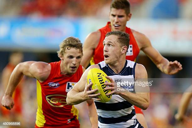 Joel Selwood of the Cats runs the ball the round 14 AFL match between the Gold Coast Suns and the Geelong Cats at Metricon Stadium on June 21 2014 in...