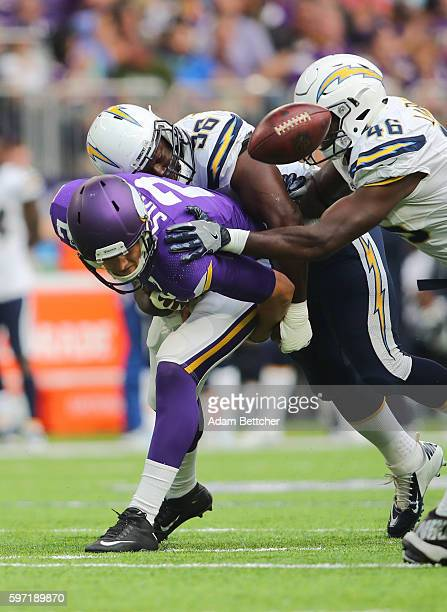 Joel Stave of the Minnesota Vikings fumbles the ball while Shaq Petteway and Chris Landrum of the San Diego Chargers apply pressure in the third...