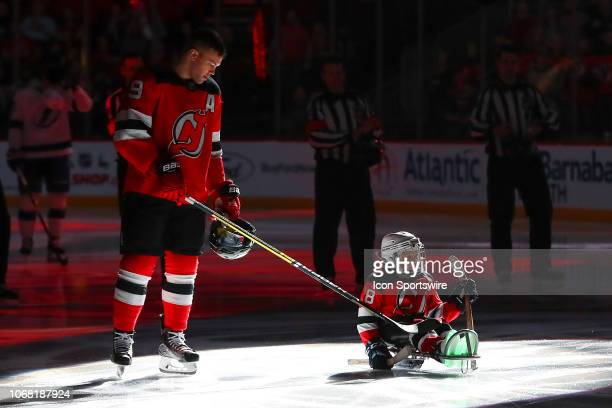Joel Tapia of the Woodbridge Warriors Sled Hockey program is helped out by New Jersey Devils left wing Taylor Hall prior to the National Hockey...