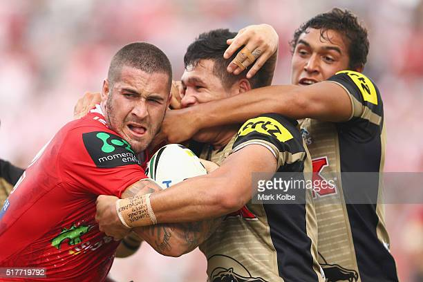 Joel Thompson of the Dragons is tackled by Tyrone Peachey and Te Maire Martin of the Panthers during the round four NRL match between the St George...