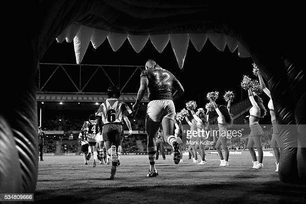 Joel Thompson of the Dragons runs out with a local junior footballer during the round 12 NRL match between the St George Illawarra Dragons and the...