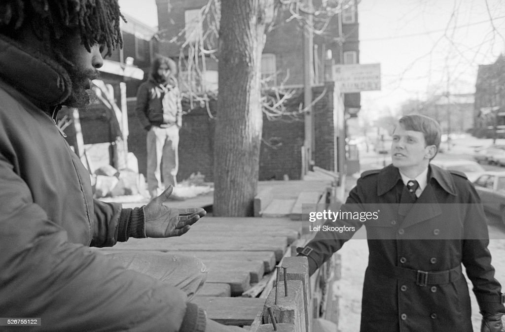 Joel Todd, a lawyer negotiator, speaks with a cult member of MOVE, to present the cities final surrender terms after a three month police stake-out of their house in the Powelton Village section of Philadelphia, Pennsylvania.