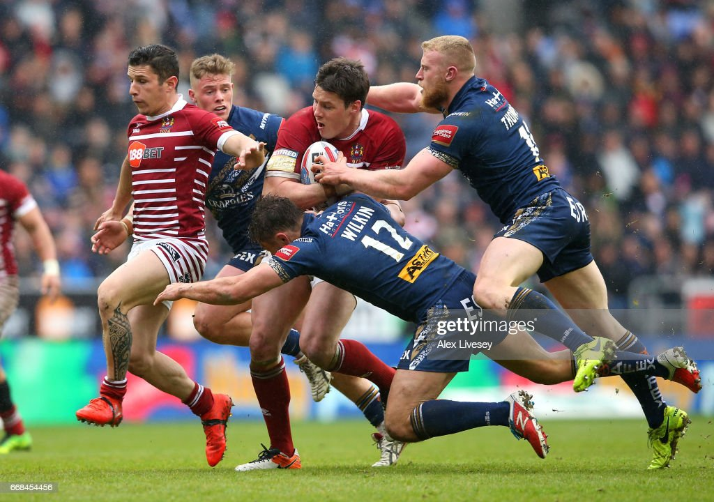 Joel Tomkins of Wigan Warriors is tackled by Jon Wilkin and Luke Thompson of St Helens during the Betfred Super League match between Wigan Warriors and St Helens at DW Stadium on April 14, 2017 in Wigan, England.
