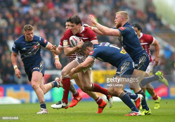 Joel Tomkins of Wigan Warriors is tackled by Jon Wilkin and Luke Thompson of St Helens during the Betfred Super League match between Wigan Warriors...