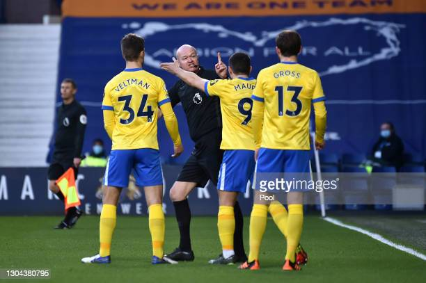 Joel Veltman, Neal Maupay, and Pascal Gross of Brighton and Hove Albion confront Referee Lee Mason as He decides to whether to award Brighton and...