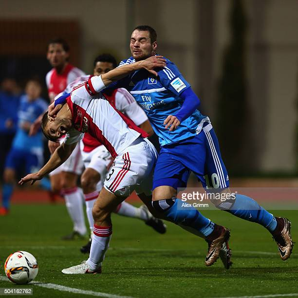 Joel Veltman of Ajax is challenged by PierreMichel Lasogga of Hamburg during a friendly match between Hamburger SV and Ajax Amsterdam at Gloria...
