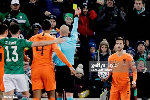 Joel Veltman of Holland receives a yellow card from referee Szymon Marciniak during the EURO Qualifier match between Northern Ireland v Holland at...