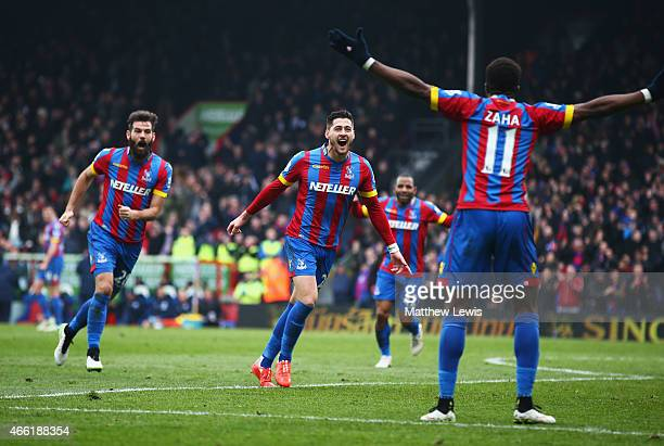 Joel Ward of Crystal Palace celebrates scoring his team's third goal with Joe Ledley and Wilfried Zaha during the Barclays Premier League match...