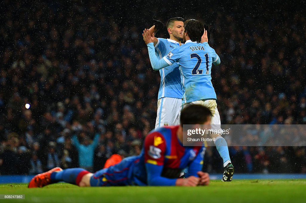 Joel Ward of Crystal Palace lies on the turf dejected as David Silva of Manchester City celebrates with team-mate Sergio Aguero after scoring his team's fourth goal during the Barclays Premier League match between Manchester City and Crystal Palace at Etihad Stadium on January 16, 2016 in Manchester, England.