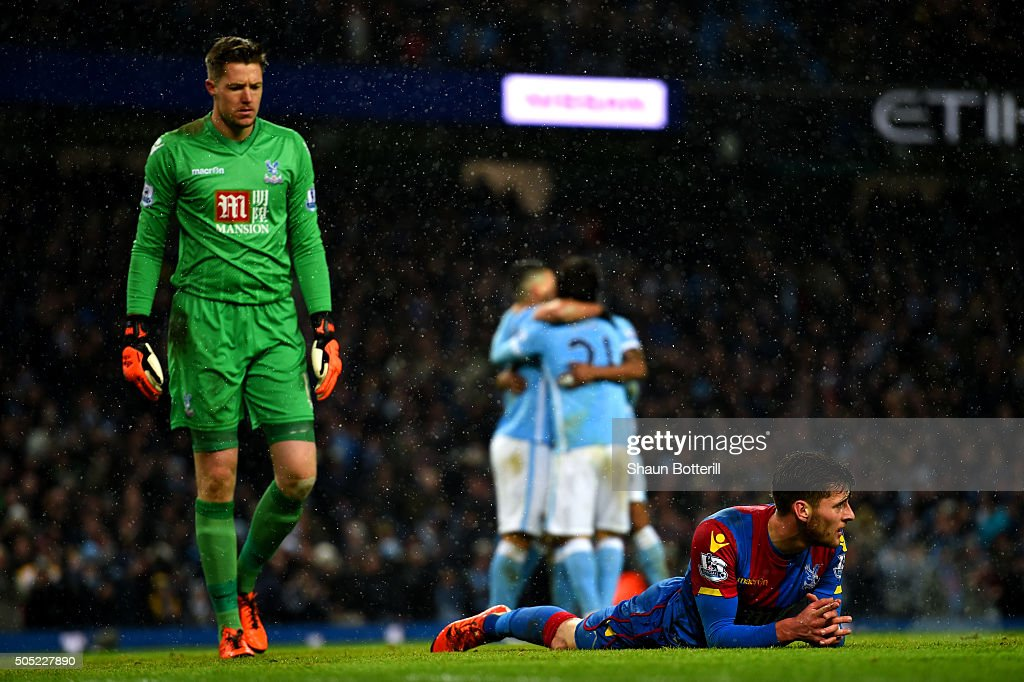Joel Ward of Crystal Palace lies on the turf dejected as Wayne Hennessey of Crystal Palace looks on after David Silva of Manchester City scored his team's fourth goal during the Barclays Premier League match between Manchester City and Crystal Palace at Etihad Stadium on January 16, 2016 in Manchester, England.