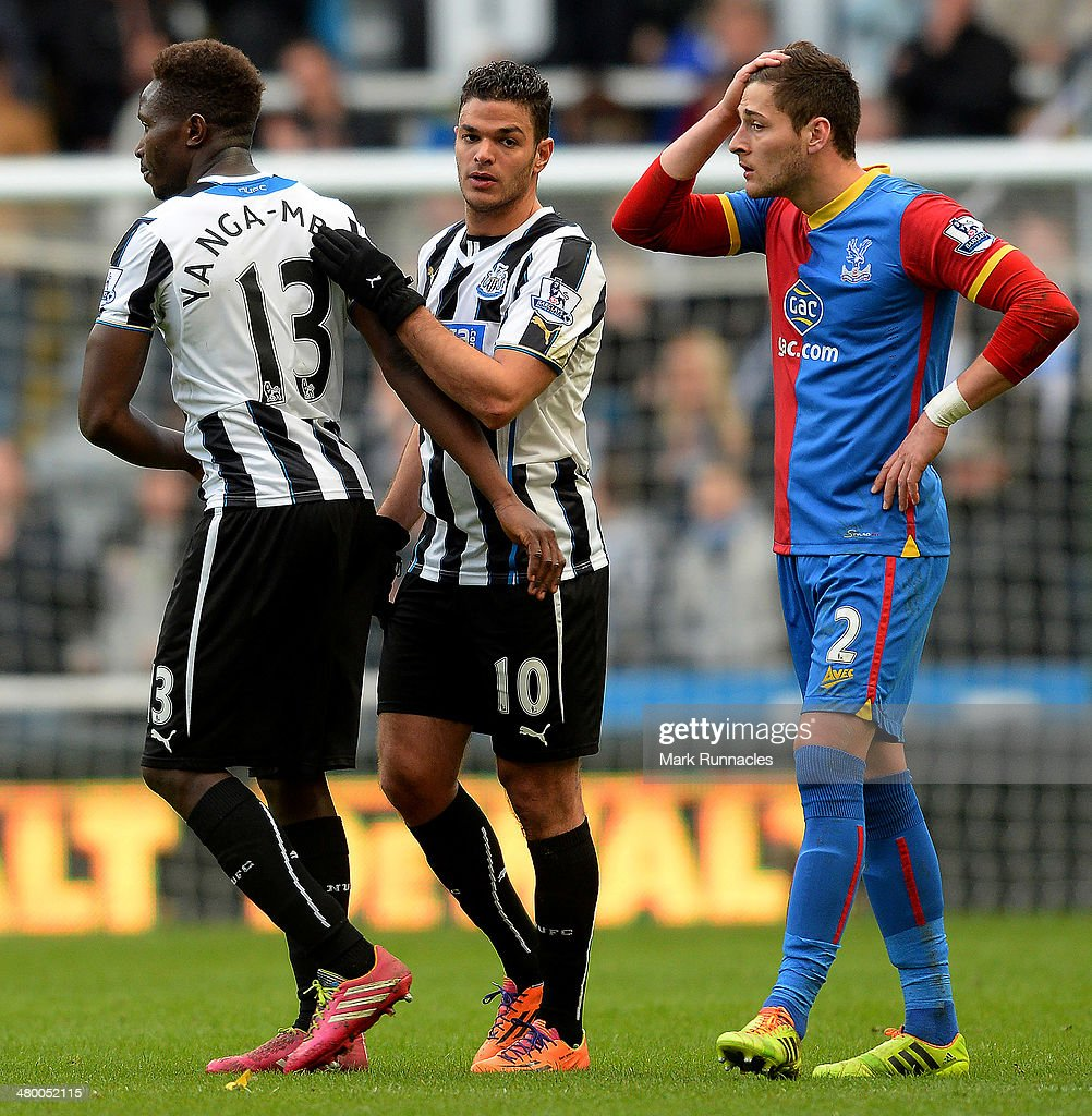 Joel Ward of Crystal Palace looks on as Hatem Ben Arfa and Mapou Yanga-Mbiwa of Newcastle embrace at the end of the Barclays Premier League match between Newcastle and Crystal Palace at St James Park on March 22, 2014 in Newcastle Upon Tyne, England.