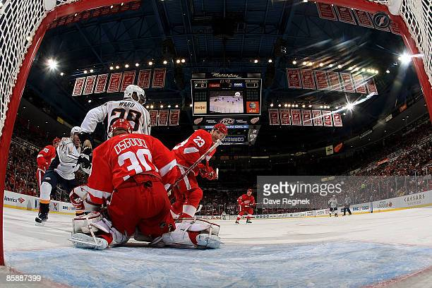 Joel Ward of the Nashville Predators screens goalie Chris Osgood of the Detroit Red Wings as defensman Brad Staurt watches the puck go in the net on...
